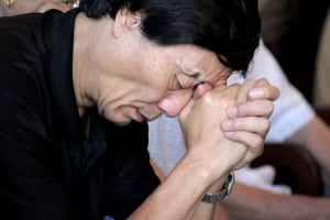 Chinese man praying despite Christian persecution in the country.